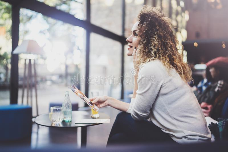 La sonrisa mujer bastante joven que hace la conversación llama con sus amigos vía el teléfono de célula mientras que envía tiempo fotos de archivo