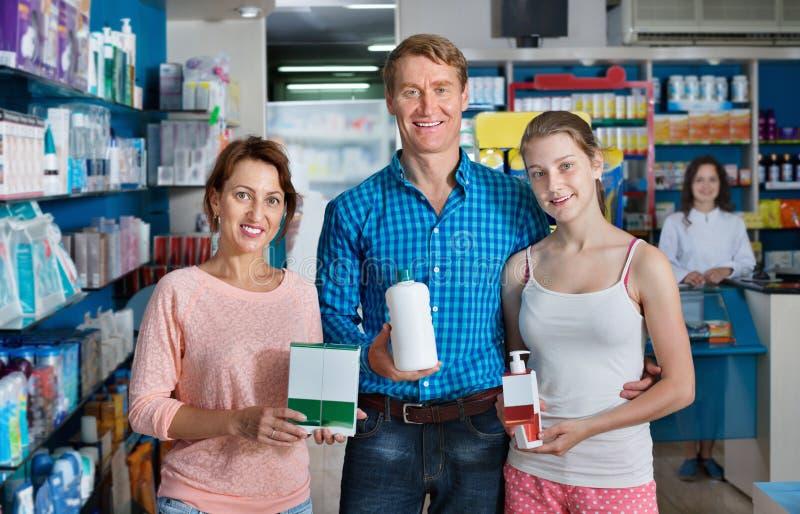 La sonrisa parents con el adolescente de la muchacha que sostiene mercancías de la farmacia fotos de archivo