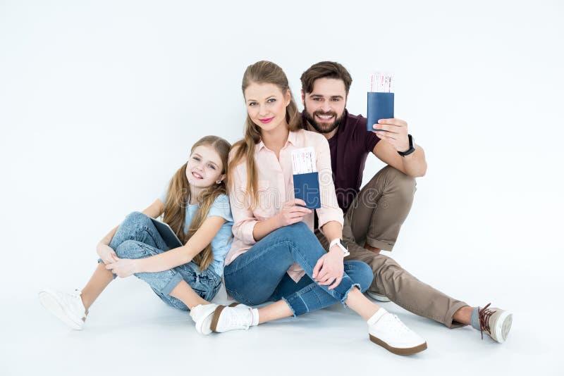 La sonrisa parents con los pasaportes y los boletos e hija con la tableta fotos de archivo libres de regalías