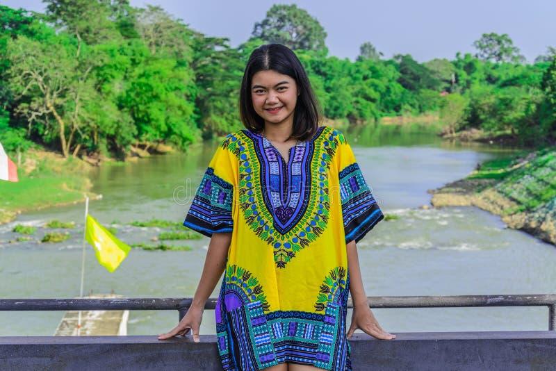 La sonrisa y la situación de la muchacha en el puente de la presa foto de archivo libre de regalías