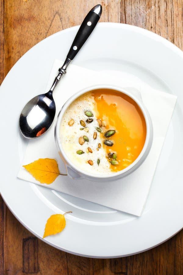 La sopa de la calabaza con las semillas de la crema y de calabaza en un cuenco blanco encendido corteja foto de archivo libre de regalías