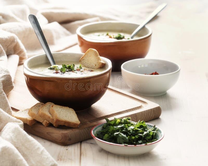 La sopa de la coliflor con el queso cheddar, el perejil y la pimienta forma escamas imagenes de archivo