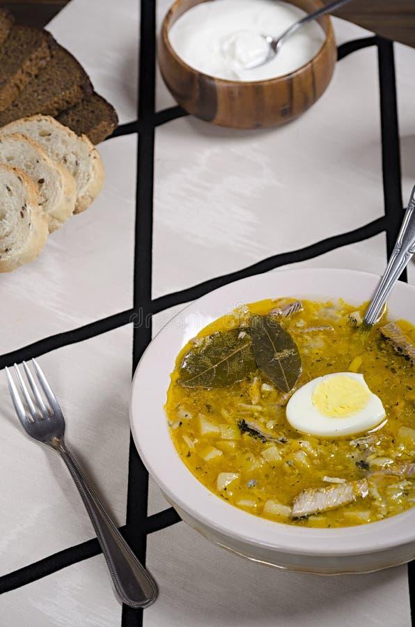 La sopa de los pescados en una placa ligera, pan blanco y negro cortó, crema agria en un cuenco de madera en un mantel rayado, he imágenes de archivo libres de regalías
