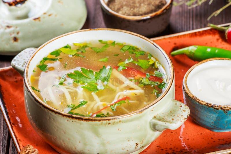 La sopa de verduras, el caldo con los tallarines, las hierbas, el perejil y las verduras en cuenco con la crema agria, especia, p fotografía de archivo libre de regalías
