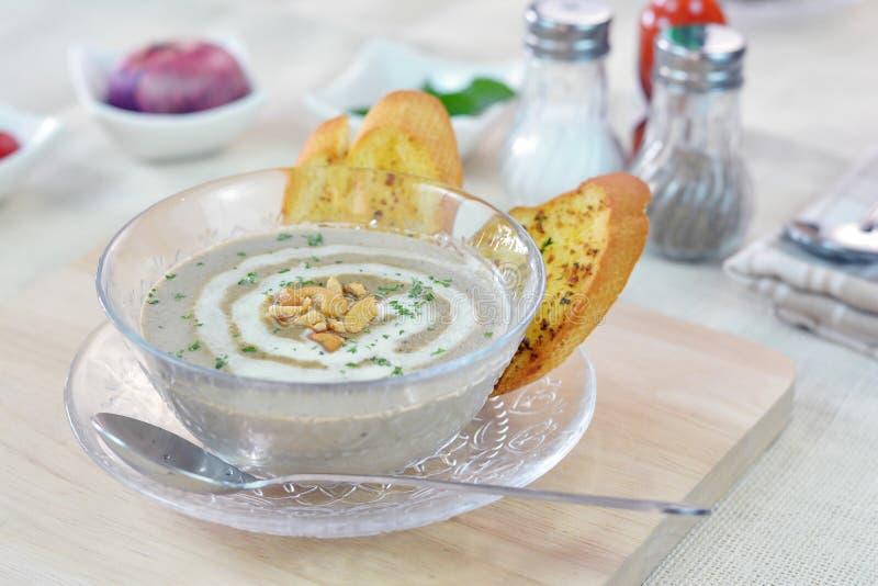 La sopa poner crema de la seta sirvió con pan de ajo en la tabla de cortar foto de archivo