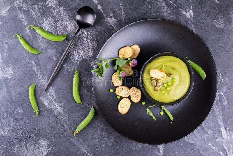 La sopa poner crema deliciosa de los guisantes verdes del verano ligero sirvió con las semillas de calabaza, cuscurrones en fondo imágenes de archivo libres de regalías
