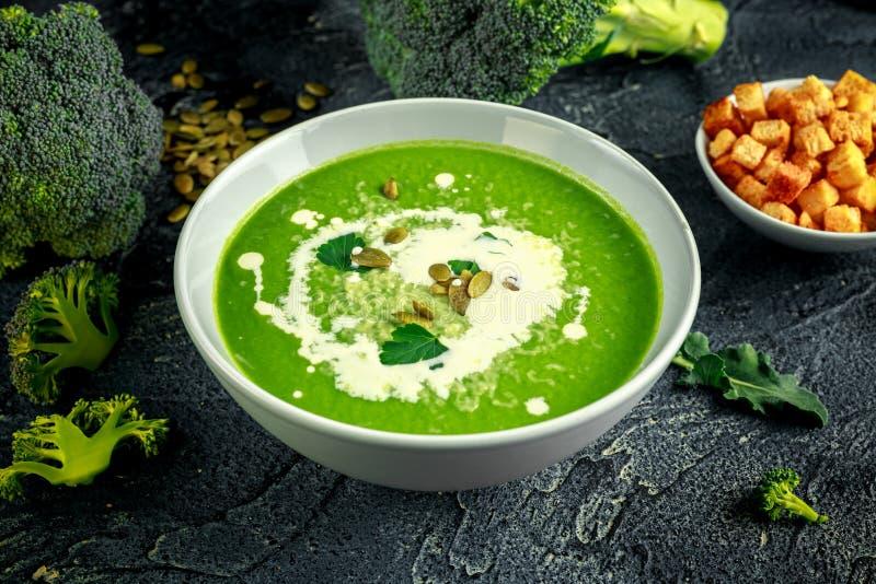 La sopa poner crema lisa del bróculi dietético con asperja de las semillas de girasol, de las hojas del perejil y de los cuscurro fotos de archivo libres de regalías