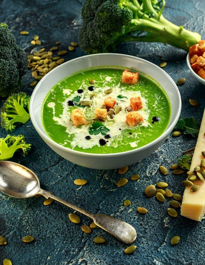 La sopa poner crema lisa del bróculi dietético con asperja de las semillas de girasol, de las hojas del perejil y de los cuscurro imagen de archivo libre de regalías