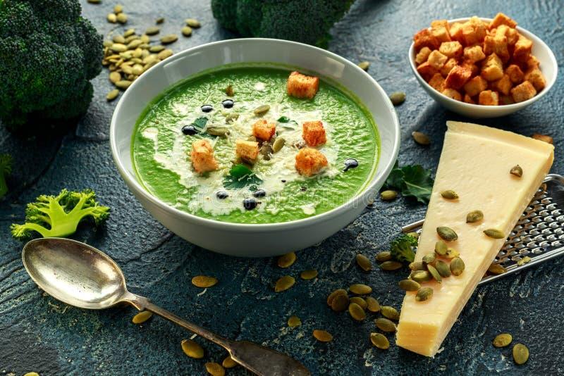 La sopa poner crema lisa del bróculi dietético con asperja de las semillas de girasol, de las hojas del perejil y de los cuscurro imágenes de archivo libres de regalías