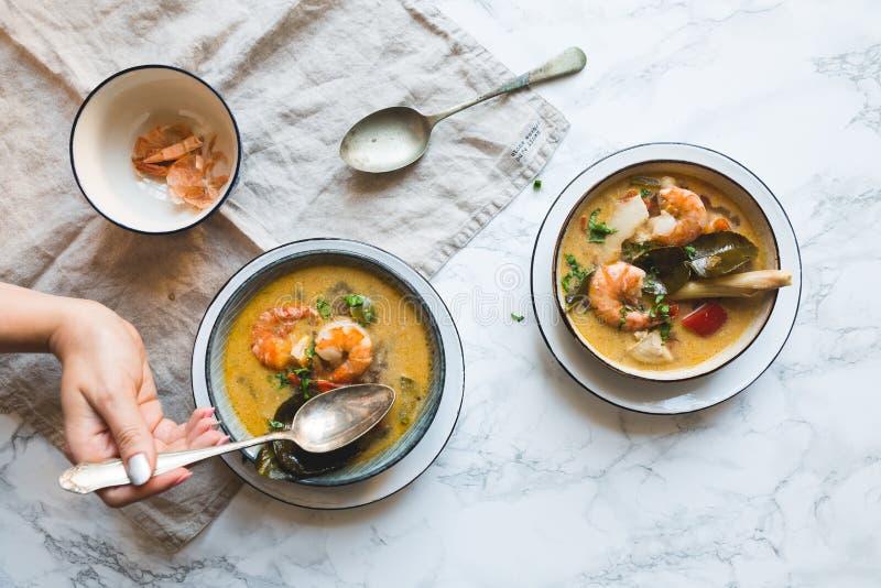 La sopa tailandesa de Tom Yum Goong con los camarones, las gambas y las hojas del cafre sirvió en una textura de mármol blanca fotografía de archivo libre de regalías