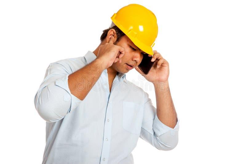 La sopraelevazione ferroviaria asiatica dell'uomo dell'ingegnere sente il suo telefono fermare un orecchio fotografia stock