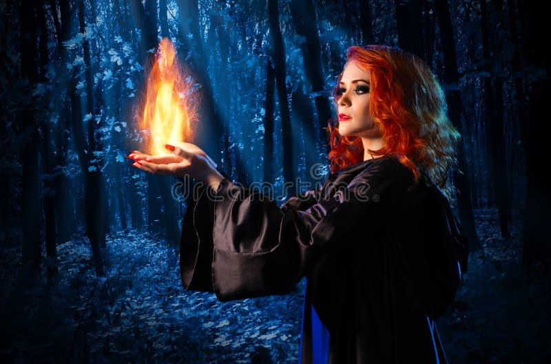 La sorcière dans la forêt de nuit tient le feu photographie stock
