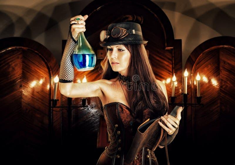 La sorcière de femme d'alchimiste prépare le breuvage magique, lit le livre magique photographie stock