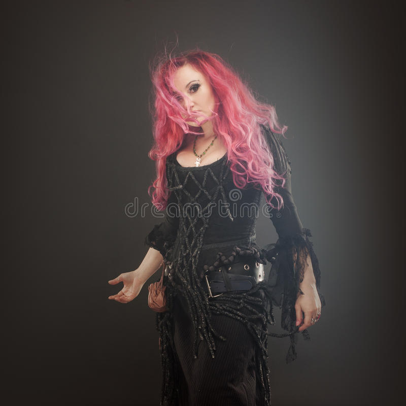 La sorcière de Halloween crée la magie Femme attirante avec les cheveux rouges dans le costume de sorcières image libre de droits