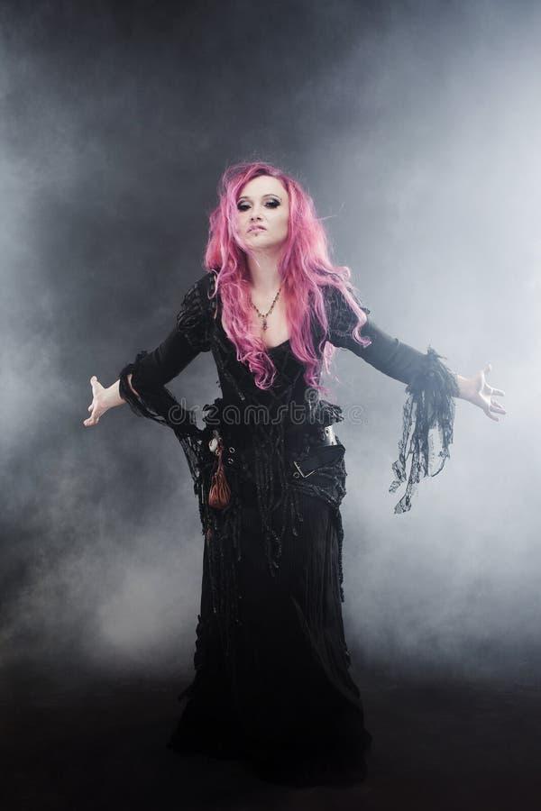 La sorcière de Halloween crée la magie Femme attirante avec les cheveux rouges dans le costume de sorcières de vaudou photographie stock