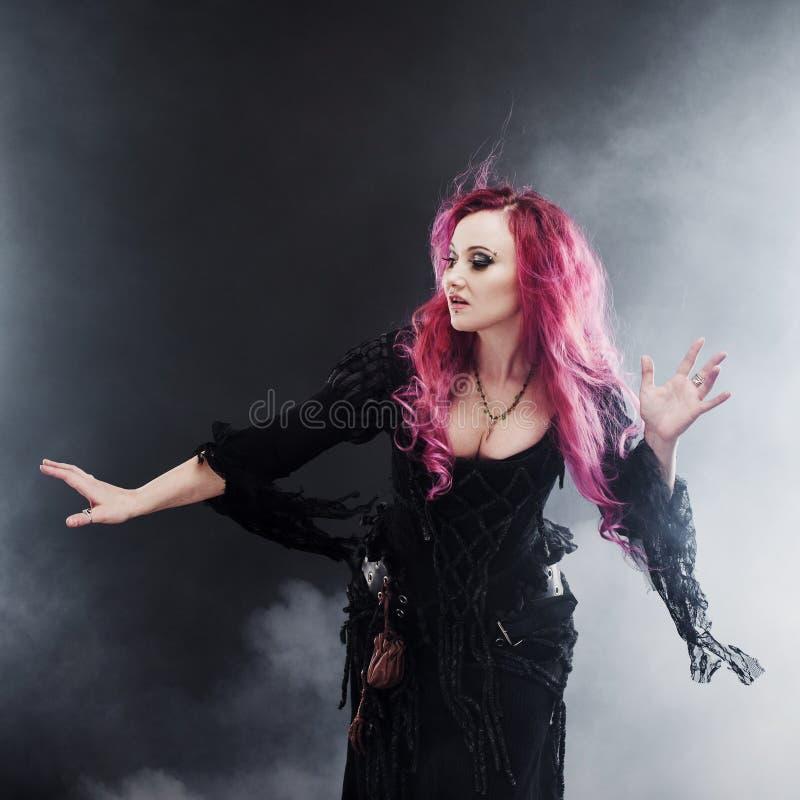 La sorcière de Halloween crée la magie Femme attirante avec les cheveux rouges dans le costume de sorcières de vaudou images stock
