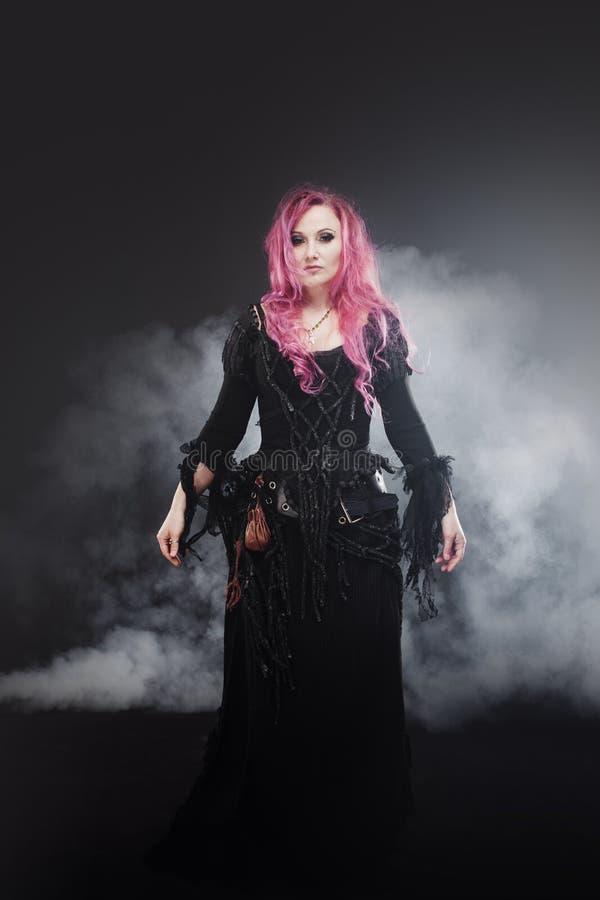 La sorcière de Halloween crée la magie Femme attirante avec les cheveux rouges dans le costume de sorcières de vaudou photo stock