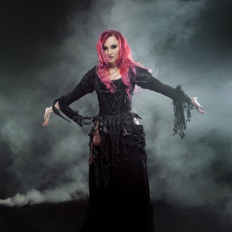 La sorcière de Halloween crée la magie La femme attirante avec les cheveux rouges dans les sorcières costument les bras tendus pa photos stock