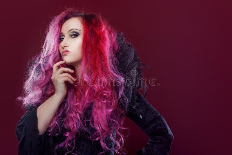 La sorcière effrayante avec les cheveux rouges exécute la magie sur un fond rose Halloween, thème d'horreur photos libres de droits