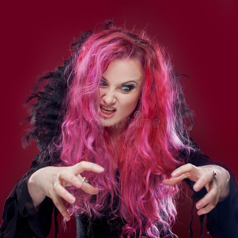 La sorcière effrayante avec les cheveux rouges exécute la magie Veille de la toussaint images stock