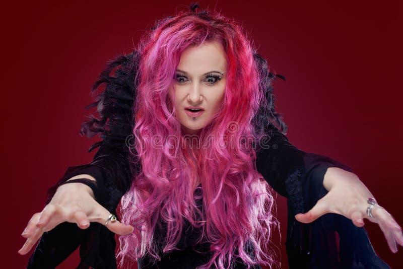 La sorcière effrayante avec les cheveux rouges exécute la magie Veille de la toussaint image libre de droits