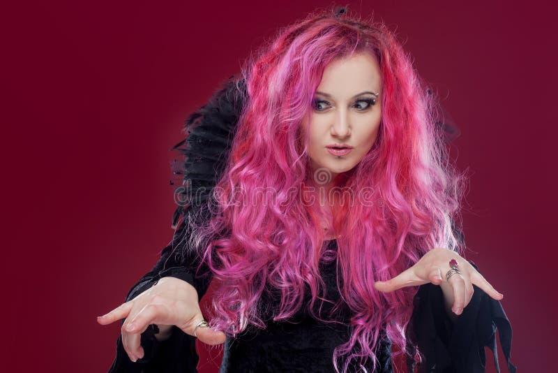 La sorcière effrayante avec les cheveux rouges exécute la magie Veille de la toussaint image stock