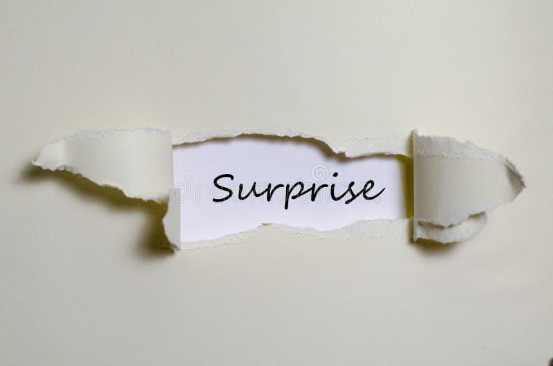 La sorpresa di parola che compare dietro la carta lacerata fotografia stock