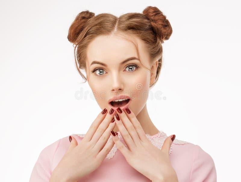 La sorpresa emocionada de la mujer sostiene mejillas a mano mirada de la cámara exp fotos de archivo