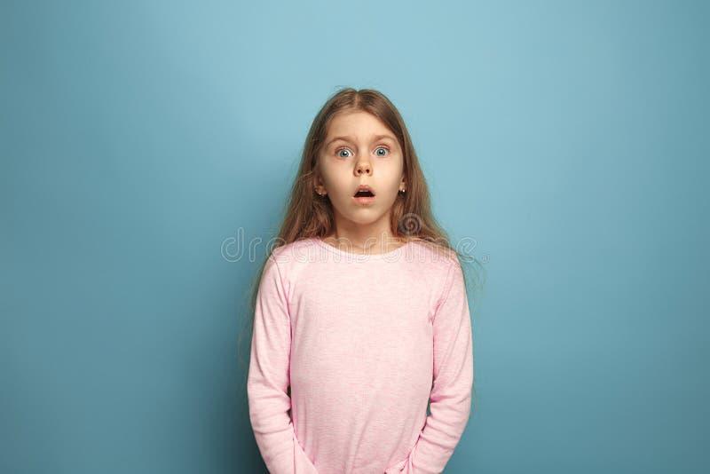 La sorpresa Muchacha adolescente en un fondo azul Expresiones faciales y concepto de las emociones de la gente imagenes de archivo