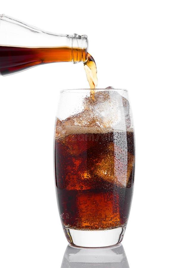 La soude se renversante de kola boivent dans le verre avec de la glace images stock
