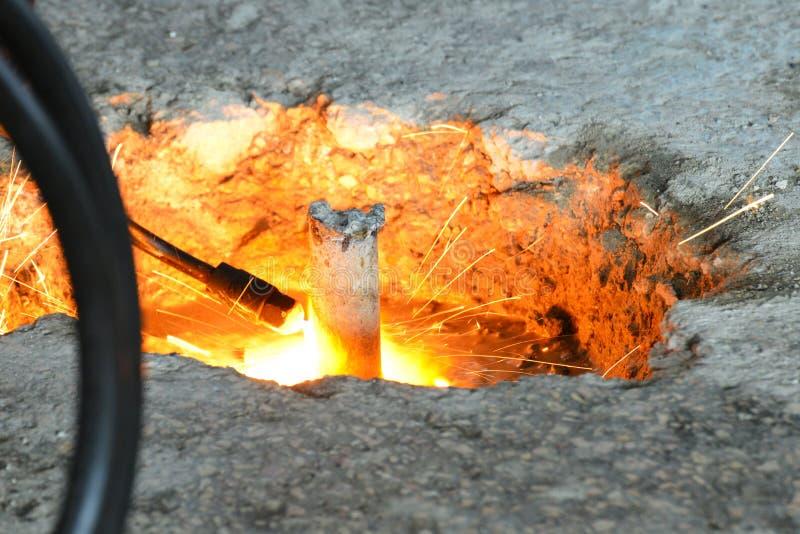 La soudeuse coupe le métal avec le soudage à gaz et les étincelles pilotent le plan rapproché images libres de droits
