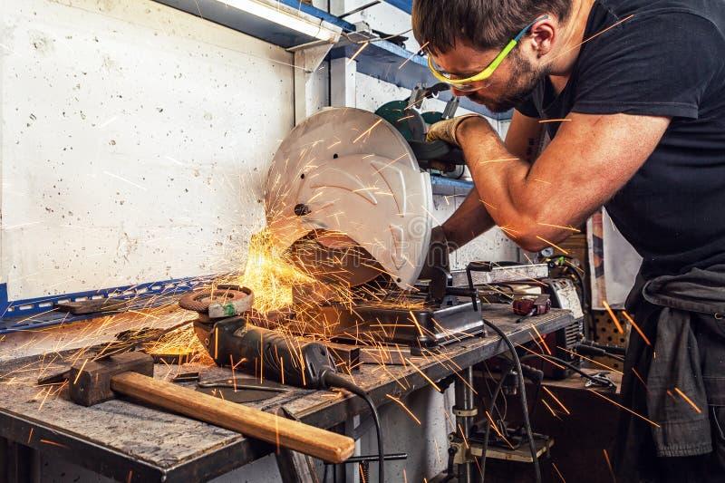 La soudeuse d'homme coupe un métal avec une scie circulaire photo libre de droits