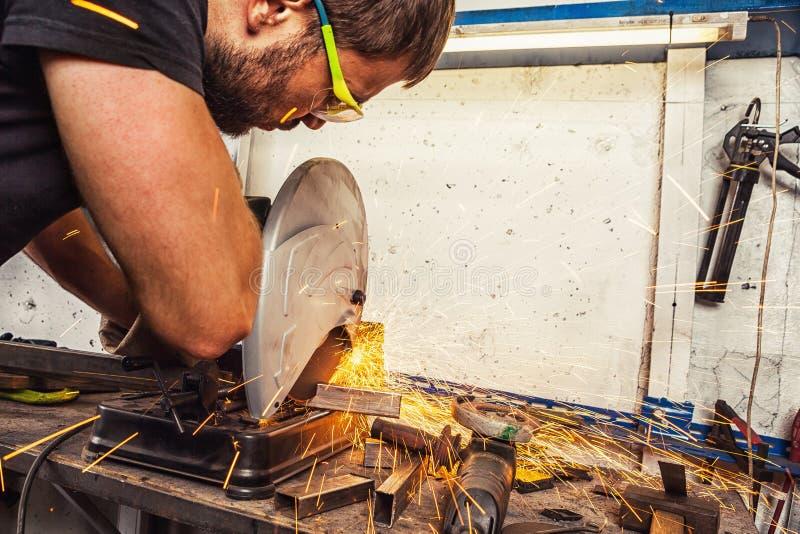La soudeuse d'homme coupe un métal avec une scie circulaire photos libres de droits
