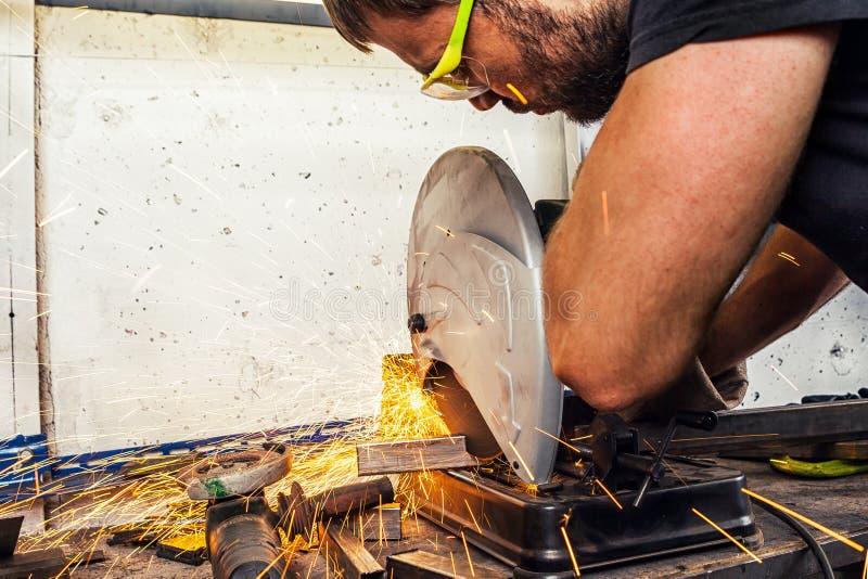 La soudeuse d'homme coupe un métal avec une scie circulaire images libres de droits