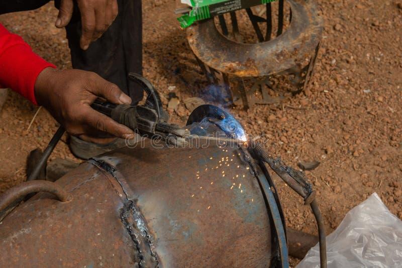La soudeuse est tuyauterie en métal de soudure dans le chantier de construction photographie stock