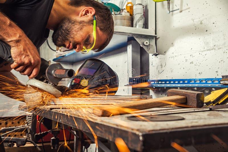 La soudeuse rectifie la broyeur d'angle en métal dans l'atelier photo libre de droits