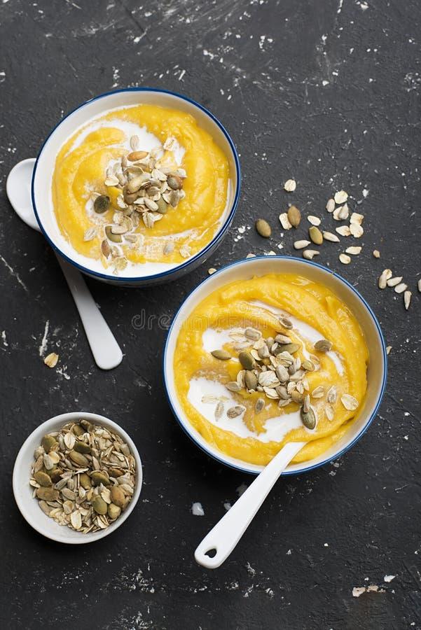La soupe à cidre de potiron et de pomme avec un écrimage des graines de citrouille grillées croustillantes, des graines de tourne photo stock