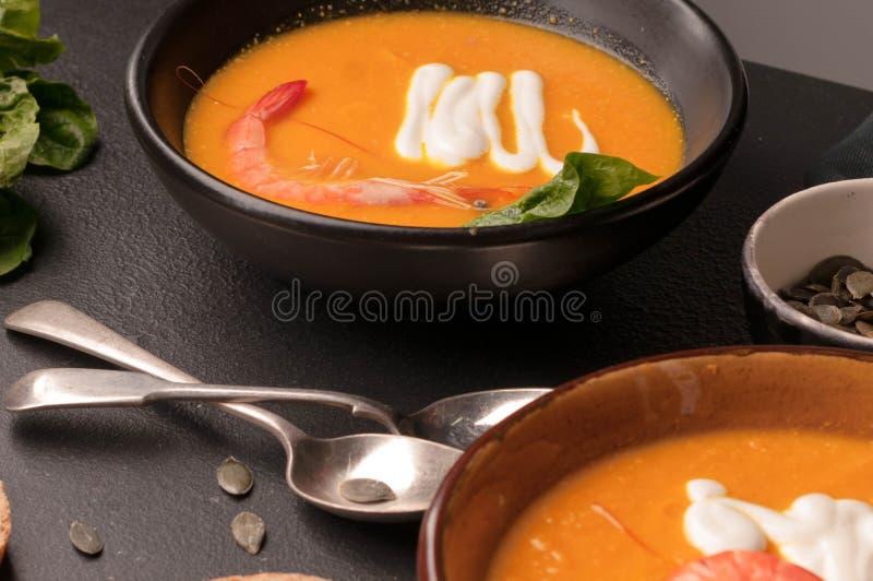 La soupe à potiron avec des crevettes, acidifient dans des cuvettes et pain foncé, verdure et des cuillères image libre de droits