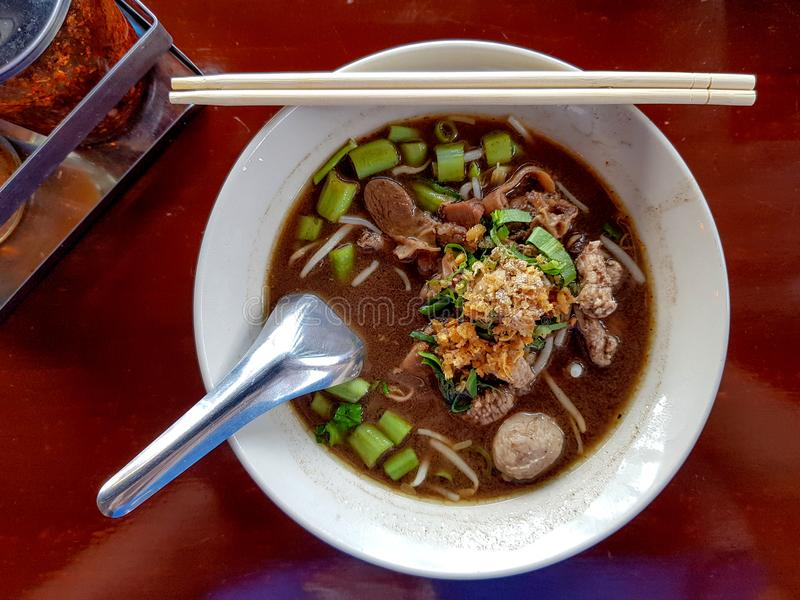 La soupe de nouilles thaïlandaise avec la boulette de viande et le porc cuits a servi dans un blanc photographie stock libre de droits