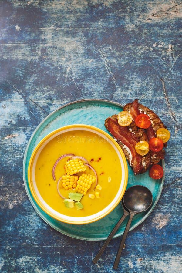 La soupe effrayante épicée à maïs et à avocat a servi avec du pain grillé de lard photo libre de droits