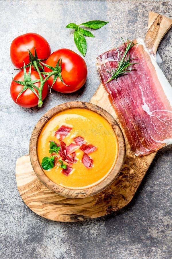 La soupe espagnole Salmorejo à tomate a servi dans la cuvette en bois olive avec le serrano de jamon de jambon sur le fond en pie photographie stock
