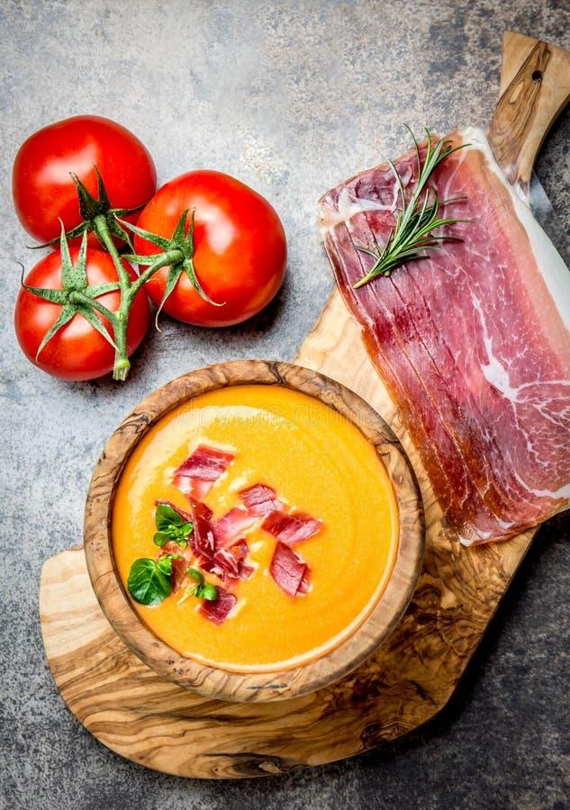 La soupe espagnole Salmorejo à tomate a servi dans la cuvette en bois olive avec le serrano de jamon de jambon sur le fond en pie images stock