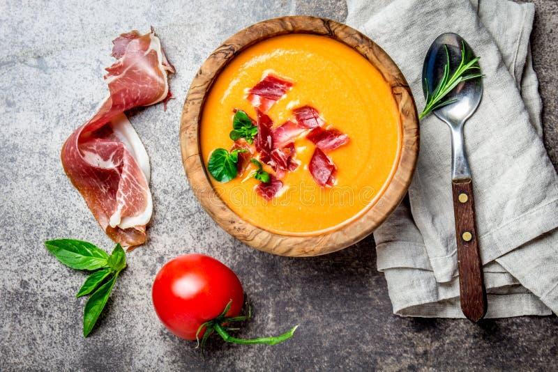 La soupe espagnole Salmorejo à tomate a servi dans la cuvette en bois olive avec le serrano de jamon de jambon sur le fond en pie image stock