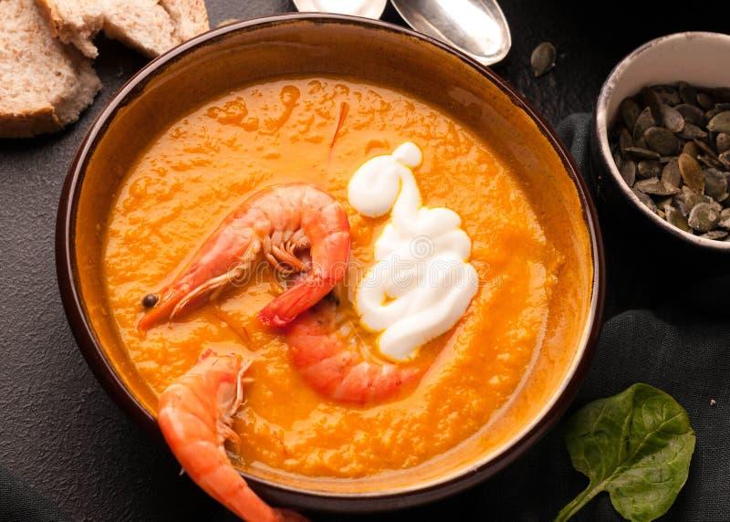La soupe orange à potiron avec des crevettes, acidifient en bowlon et pain foncés photos stock