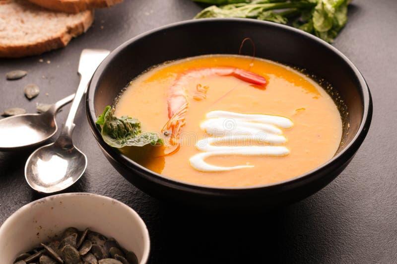 La soupe orange avec la crevette, acidifient en bowlon et pain foncés près des cuillères d'argent images stock