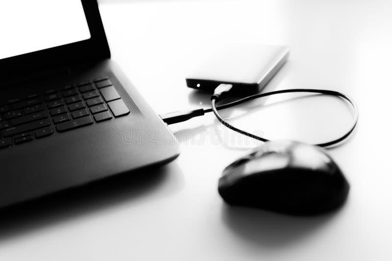 La souris noire et blanche de hdd d'ordinateur portable sur le bureau est brouillée photo libre de droits