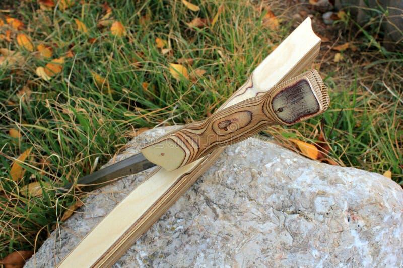 La spada di legno della guaina sta su un supporto su una pietra fotografia stock libera da diritti