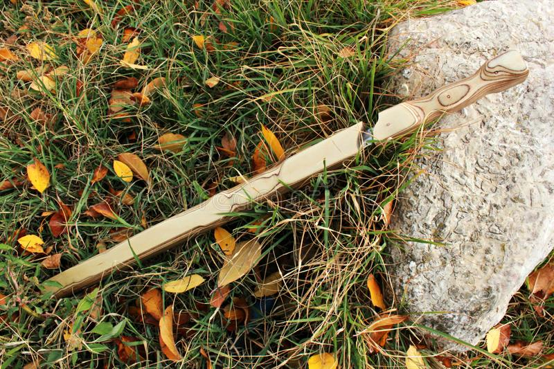 La spada di legno della guaina sta su un supporto su una pietra fotografia stock