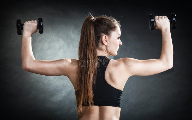 La spalla di addestramento della ragazza di forma fisica muscles le teste di legno di sollevamento indietro osserva fotografia stock