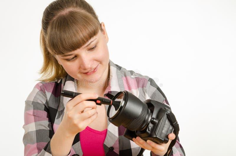 La spazzola del fotografo pulisce la parte anteriore della lente sulla macchina fotografica immagine stock